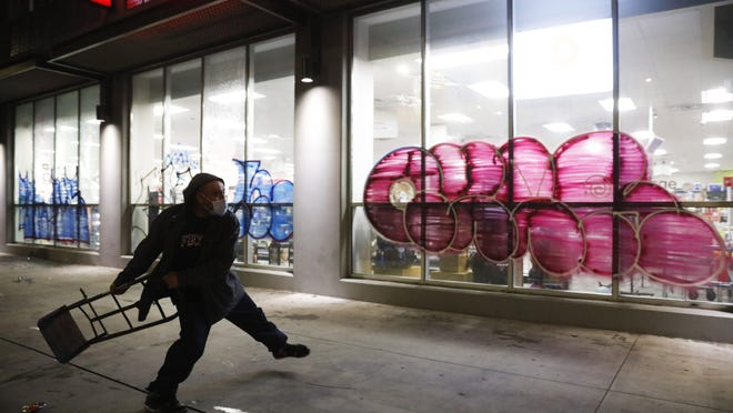 A man throws a hand truck into the window of vandalized CVS store during a protest over the death of George Floyd on  Saturday, May 30, 2020, in Los Angeles. The pharmacy chain has closed stores in 20 states, including a store in Downtown Columbus, amid the unrest.