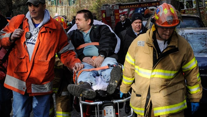 In this photo taken on Sunday, Dec. 1, 2013, Metro North Railroad engineer William Rockefeller is wheeled on a stretcher away from the area where the commuter train he was operating derailed in the Bronx borough of New York. The National Transportation Safety Board reported Monday that the train Rockefeller was driving was going 82 mph around a 30-mph curve when it derailed killing four people and injuring more than 60. (AP Photo/Robert Stolarik)