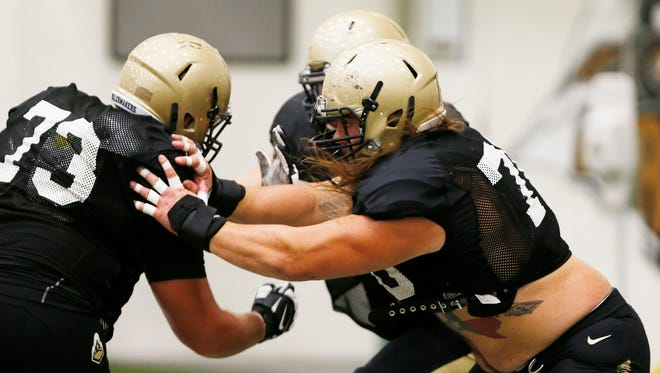 Ryan Flaherty, from left, Jordan Roos and Matt McCann, background, take part in blocking drills during football practice Monday, August 15, 2016, in the Mollenkopf Athletic Center on the campus of Purdue University.