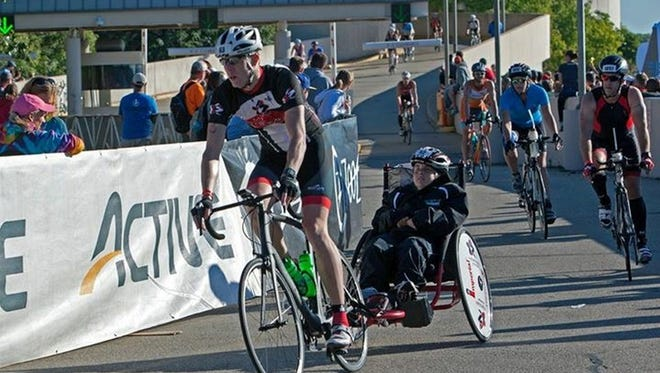 With Chris Engstrom of Green Bay riding in a race chair, Eric Johnson of De Pere rides a bicycle during the second leg of the Ironman Wisconsin 2016 triathlon in Madison on Sunday.