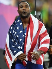 Justin Gatlin wears the US flag around his shoulders after his win in the men's 100-meter final at the London Stadium on Aug. 5, 2017.