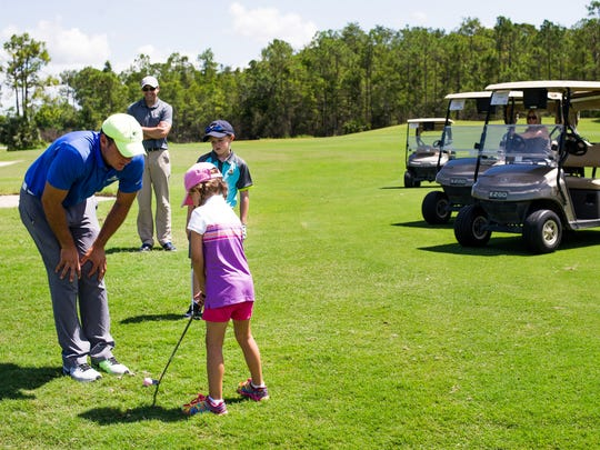 Ava Becker, 5, gets instruction from Jordan Ball, left, as her family watches during a junior summer golf camp at Stoneybrook Golf Club in Estero, Fla. on Monday, July 25, 2016.