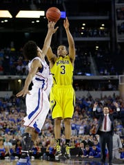 This March 29, 2013 file photo shows Michigan's Trey Burke (3) making a three-point basket in the final seconds of the second half of a regional semifinal game against Kansas in the NCAA college basketball tournament in Arlington, Texas. Michigan freshman Jordan Poole's buzzer beater, which gave the Wolverines a 64-63 victory and set up Thursday's matchup with Texas A&M in Los Angeles, is drawing comparisons to Burke's shot against Kansas in the 2013 regional semifinals.