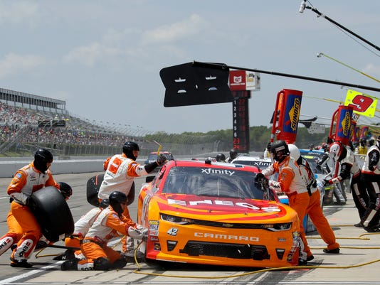 Crew members work on the car of Kyle Larson during a pit stop in the NASCAR xfinity Series auto race, Saturday, June 10, 2017, in Long Pond, Pa. (AP Photo/Matt Slocum)