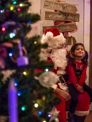 A girl sits on Santa's lap at the Frontier Homestead