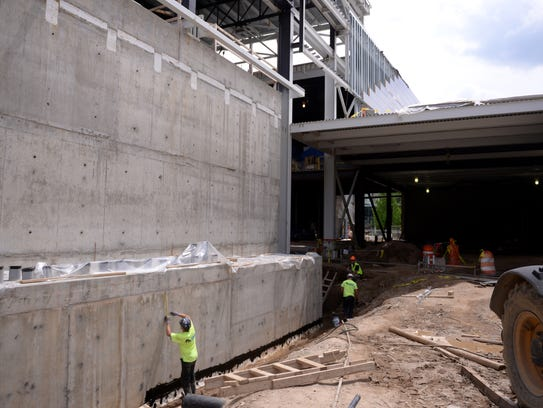 Construction crew members work at the Facility for