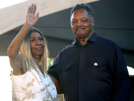 Aretha Franklin and the Rev. Jesse Jackson wave to