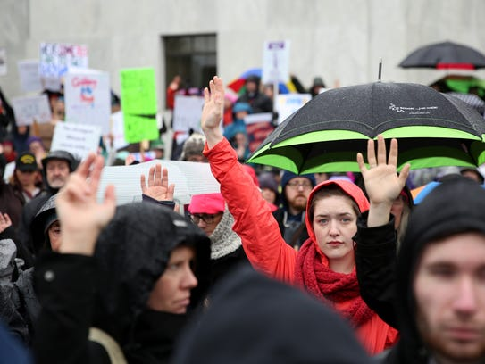 People raise their hands to signify #MeToo during the