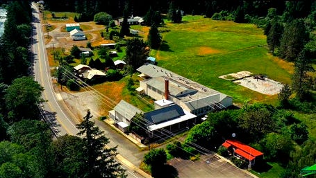 This undated aerial photo taken from a drone video and provided by LandandWildlife.com, shows Tiller, Ore. Almost all of the downtown in Tiller, a dying timber town in remote southwestern Oregon, is for sale for $3.5 million and the elementary school is for sale separately for $350,000. The asking price of $3.5 million brings with it six houses, the shuttered general store and gas station, the land under the post office, undeveloped parcels, water rights and infrastructure that includes sidewalks, fire hydrants and a working power station.