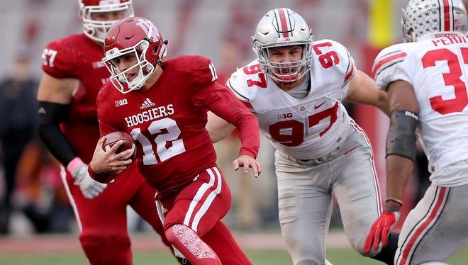 Hoosiers quarterback Zander Diamont (12) runs by Ohio State Buckeyes defensive lineman Joey Bosa (97) in the fourth quarter.