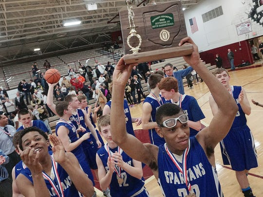 St. Peter's Tyson Kent holds up the District Championship trophy after the team defeated St. Mary's Central Catholic 57-52 at Willard High School on March 4.