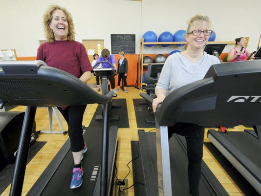 Jan Matthews, left, and Nancy Williams-Smith joke around while working out at the YWCA. Williams-Smith donated her kidney to Matthews and the duo along with their friend, Leslie Bentz, rear left, are training for the Y Tri triathlon. The trio have been friends since 7th grade and have celebrated the successful kidney transplant annually. (Jason Plotkin - Daily Record/Sunday News)