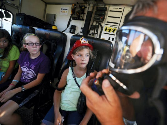 East Prospect firefighter Marlin Mellinger, right, explains his breathing apparatus to a rapt audience from left Courtney Kmett, 12, of Mount Wolf, Mackenzie Wagaman, 12, of Red Lion, and Haley Sprinkle, 11, of York Township, during Community Hero Night at Grace Baptist Church in Windsor Township Wednesday.