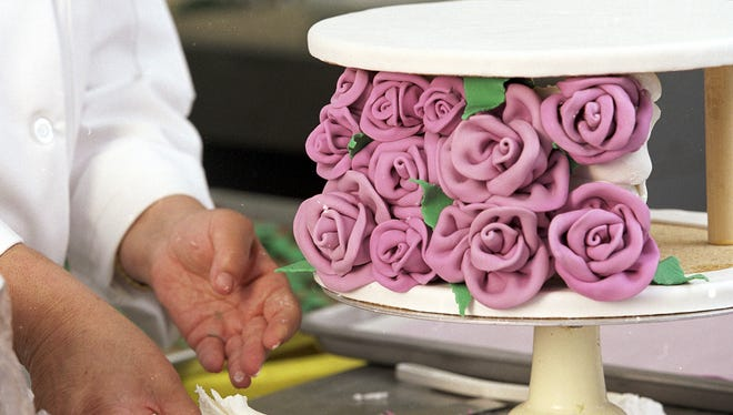 Royale Icing owner Margaret Lastick attaches fondant decorative roses for a $5,000 wedding cake.