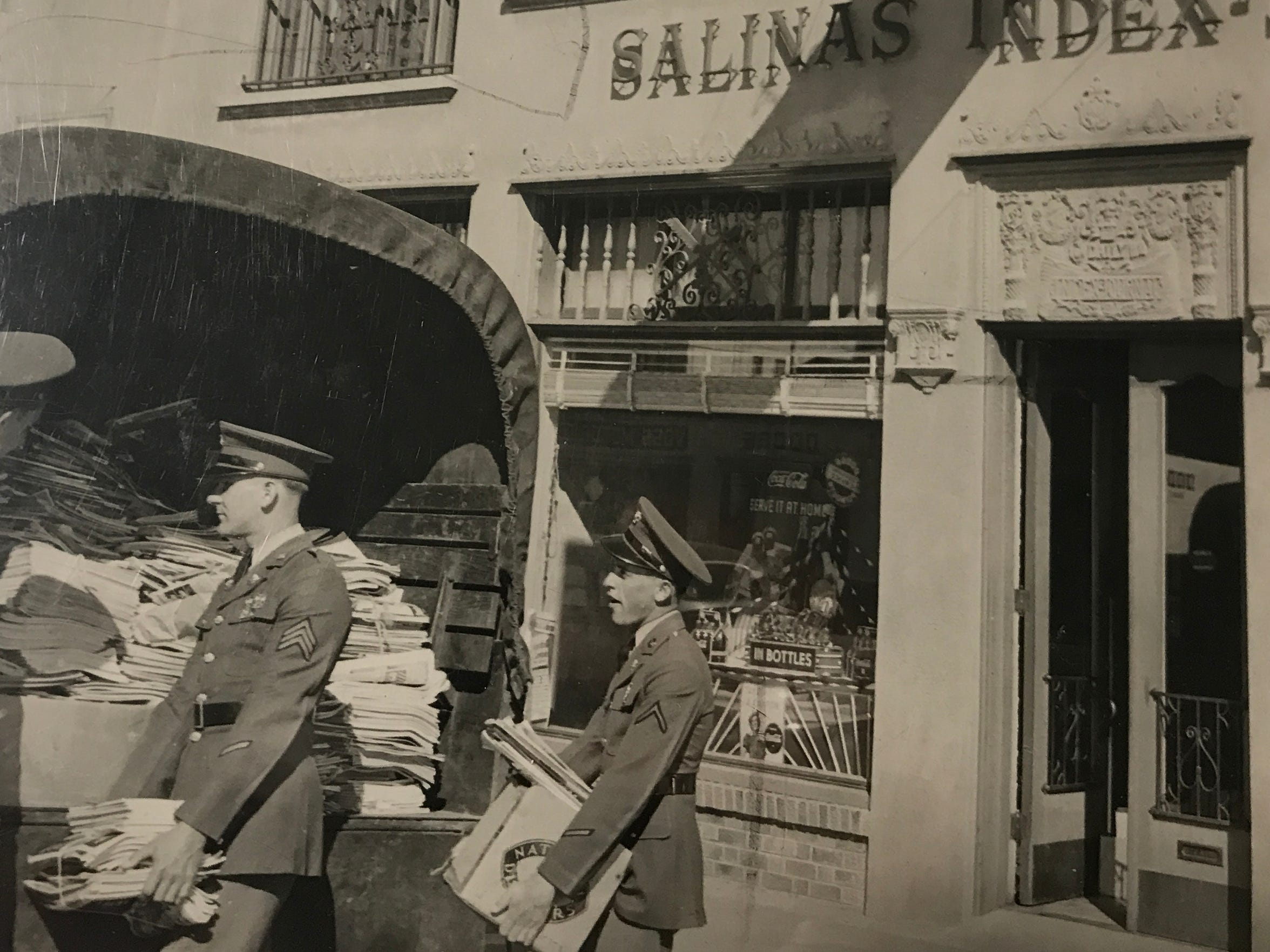 Men carry newspapers out from the Salinas Index during
