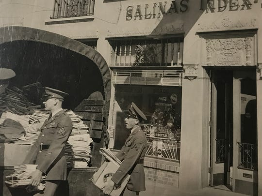 Men carry newspapers out from the Salinas Index during World War II.