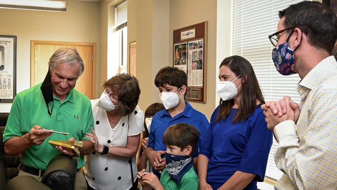 Rockford Register Star Opinion Editor Wally Haas, left, looks over a key to the city on Tuesday with his wife, Mary; grandchildren, Audrey, Owen and Evan Olvera; and daughter, Renee Olvera. Mayor Tom McNamara, right, presented Haas the key as the longtime editor prepares to retire after more than 40 years with the newspaper.
