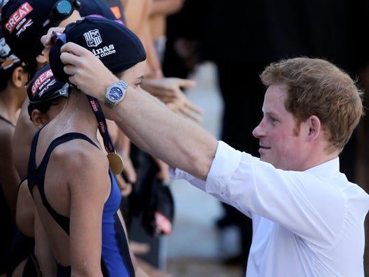 Britain's Prince Harry places a medal on a young swimmer after an exhibition swim during his visit to the Minas Tenis Club where England's Olympic team will practice during the 2016 Olympic and Paralympic Games in Belo Horizonte, Brazil, Tuesday, June 24, 2014. Prince Harry is in Brazil for the World Cup. (AP Photo/Bruno Magalhaes)