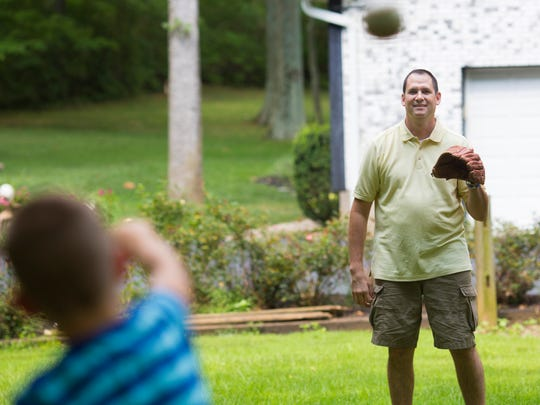 Paul Rinderknecht plays catch with his son Leo in their