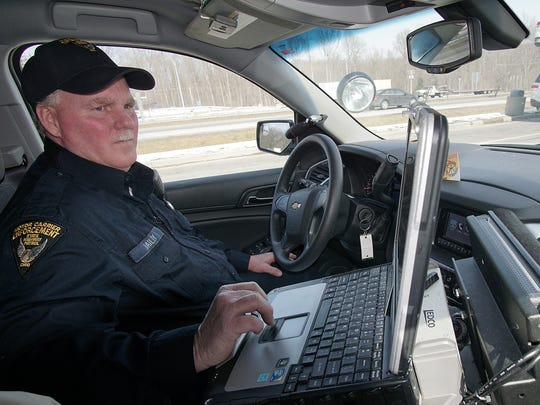 Don Dailey, Commercial Motor Carrier Inspector for the Ohio Highway Patrol, checks the information of a diver on his computer at the US 30 rest stop West of I-71 Friday, February 19th.