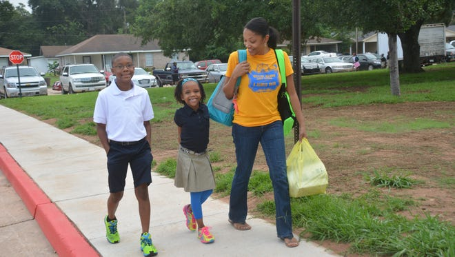 Xzavier Watkins (left) and his sister, Melanie Johnson, walk to Martin Park Elementary School with mom Vanessa Johnson on the first day of school in Rapides Parish Tuesday.