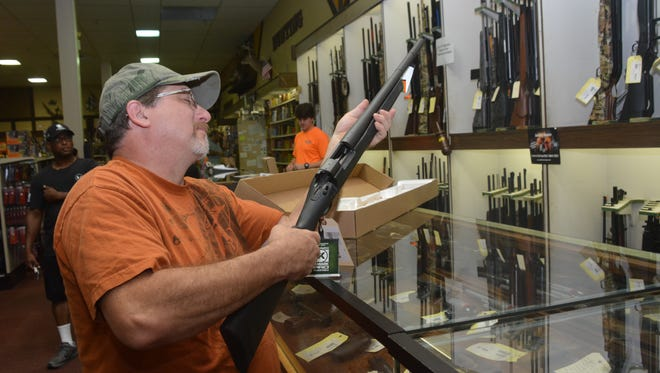 Christopher Mahfouz of Alexandria looks at a Remington rifle Saturday at Security Sporting Goods in Alexandria. He purchased the rifle but did not have to pay state and local sales tax because of the Second Amendment Weekend Sales Tax Holiday, which began Friday and runs through Sunday.