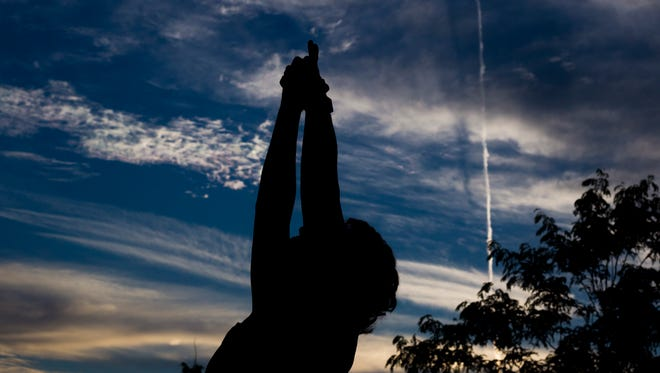 A student performs a pose during the free sunrise yoga class at Liberty Park on May 17, 2017.