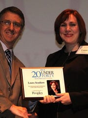Bridge Community Health Clinic Executive Director Laura Scudiere accepts her 20 Under Forty award at the November 2014 award luncheon in Wausau.