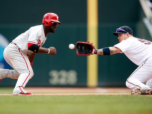 Minnesota Twins first baseman Byung Ho Park, right, of South Korea, reaches for the ball before tagging out Philadelphia Phillies' Odubel Herrera on a pickoff in the forth inning of a baseball game Thursday, June 23, 2016, in Minneapolis. (AP Photo/Jim Mone)