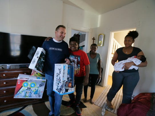 (left) Kevin Garrison of Atlantic Highlands, who runs the charity, Blessing Bag Brigade NJ, and recently renovated Hattie Hunter's home at no cost, brings gifts to Hunter's five great-grandchildren
