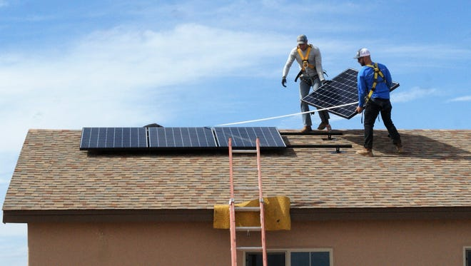 Installers from Positive Energy Solar position the final module on a new home in Columbus, New Mexico.