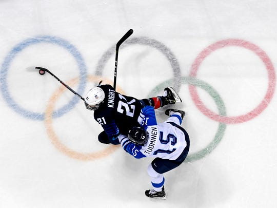 United States forward Hilary Knight (21) moves the puck against Finland defenseman Minnamari Tuominen (15) during the Pyeongchang 2018 Olympic Winter Games at Gangneung Hockey Centre.