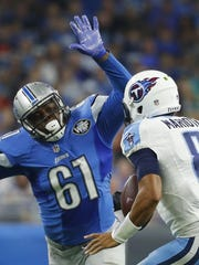 Lions defensive end Kerry Hyder (61) chases Titans quarterback Marcus Mariota (8) during the first half Sunday.
