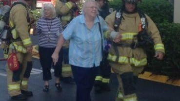 Firefighters help Trinity Towers residents from the building.