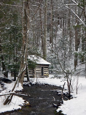 The Oliver Tipton Cabin in the Smokies is covered in snow. The new superintendent open house set for Thursday has been postponed for inclement weather.