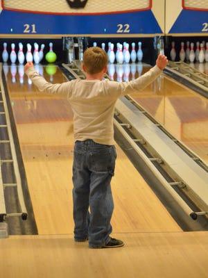 A boy watches his ball knock down some pins at Northgate Bowl.