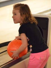 A girl picks up her ball at Northgate Bowl.