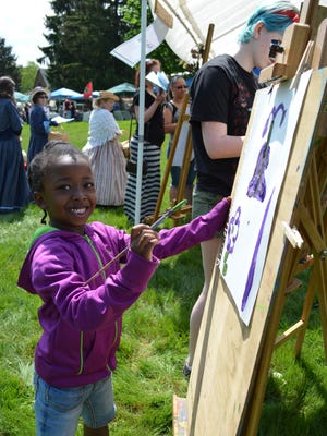 Aisha Clarke, 5, of Vineland creates a painting at the Kids-n-Art Tent set up by Magnolia Hill Studios at Founder's Day in 2014.