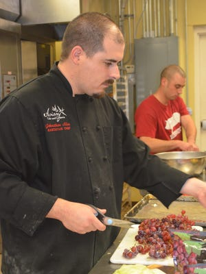 John Allen, executive chef at The Aviary, prepares for a catering event. The restaurant is one of many affected by rising food costs. In response, the restaurant offers more specials and a new menu and has cut staff slightly.