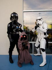Las Cruces Star Wars fans Bryan Turnbow, 40, and his son Daniel Turnbow, 8, are joined by Cody Turnbow, 36, from Capitan to attend the ticket presale event at the Cineport 10 on Saturday. They made their own costumes. Bryan wears the white Storm Trooper costume, and his brother Cody is wearing the black TIE fighter pilot uniform. Daniel is dressed as a jawa.