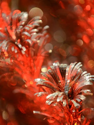"""File - The tip of an aluminum tree reflects the red color from a color wheel light at The Flower Gallery for the """"Evergleams on Eighth"""" event in 2015."""