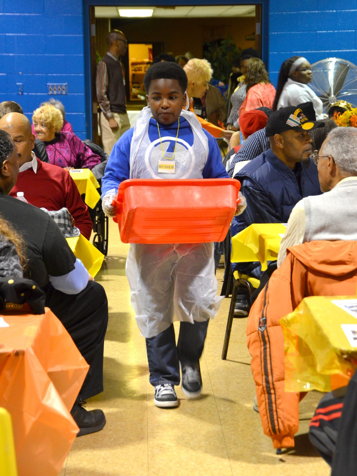 Donnell Adams Jones roams the aisles as he clears tables at the annual Thanksgiving dinner.