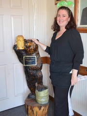 Shawna Chatten of Bridgeton shows the hand-carved wooden bear that was part of the decor at Millville's Gil Bears Tavern, which was destroyed by fire.