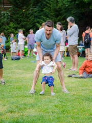 Jason Rudman of Cleveland, Ohio, plays with his son Roman, at Provincetown's Family Week, the largest annual gathering of LGBTQ parents and their families in the world, held each year in the Rhode Island coastal town.
