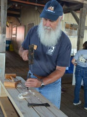 Karl Kramer of Alloway demonstrates the use of ship building tools during Maritime Heritage Day at the Bayshore Center. Ship builders filled the cracks between the planks of wood with materials like cotton and rope. Photo/Jodi Streahle