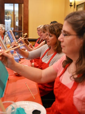 """Julie Nolden, Mindy Kahlenberg,Suzanne Steimle andJodi Schamburek fill in the backgrounds of their painting at a """"Picasso and Pub"""" night at the Courthouse Pub in Manitowoc on Monday, July 18."""