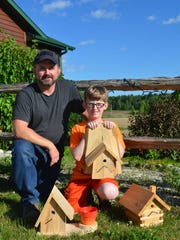 Zach and Michael Boldt pose with several of the wooden birdhouses they make to raise money for the MS Walk charity.