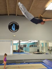 Savannah Thompson, former Olympian and owner of Hangtime Gymnastics, demonstrates some trampoline moves during a class on August 11, 2016.
