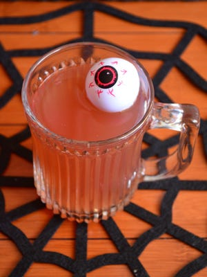 """A plastic eyeball is an inexpensive way to transform a delicious mulled wine into a """"Witches Brew"""" for your Halloween party. These eyeballs are freaky sticking out of a cheeseball, too."""