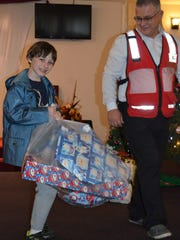 Kurt Grehlinger, 9, of Clayton carries a bag of gifts